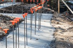 Line of rebar in poured concrete footing with orange caps Stock Photo