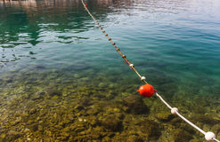 Line of red buoys on the rope floating Stock Photo
