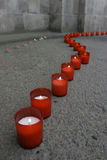 Line of red candles. On pavement, outside a church, at dusk royalty free stock photography