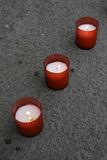 Line of red candles. On pavement, outside a church, at dusk royalty free stock images