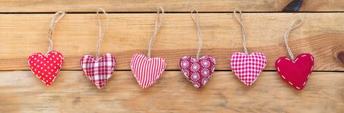 Line of red fabric hearts hanging on ood background. Line of red fabric hearts hanging on old wood background royalty free stock photography