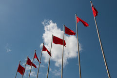 Line of red flags in front of cloudy blue sky Royalty Free Stock Images