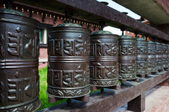 Line of religious prayer wheels. Day Stock Images