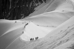 Line of roped-up teams of mountaineers on the ridge descending from Aiguille du Midi cable car station royalty free stock photo