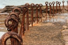 Line of rusty chain link posts on a sunny day at sea baths. Long line of rusty chain link posts on a sunny day at sea baths Stock Image