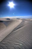 A Line in the Sand. Against bright blue sky and flaring sun Stock Image