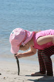Line in the Sand. Little girl drawing in the sand of the beach with a stick royalty free stock image