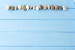 Line of sea stones on a wooden table Royalty Free Stock Images