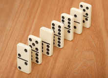 Line from seven dominoes on wooden surface Royalty Free Stock Photography
