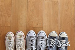 A line of several pairs of vintage sneakers on a wood floor. Stock Image