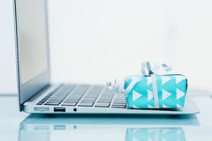 On line shopping. Gift box with silver bow on light background next to the computer. On line shopping Stock Image