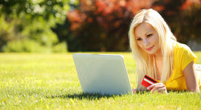 On-line Shopping. Smiling Blonde Girl with Laptop, Credit Card. On-line Shopping. Smiling Blonde Girl with Laptop and Credit Card Lying on Green Grass. Outdoor Royalty Free Stock Image