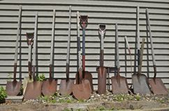 A line of shovels and spades in a line. An assortment of old rusty spades and shovels lean against the siding of a building Stock Image