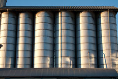 Line of silos. Row of metal silos under a roof with radent sunlight with contrast and light reflex Royalty Free Stock Image