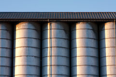Line of silos. Row of metal silos under a roof with radent sunlight with contrast and light reflex Royalty Free Stock Photography