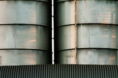 Line of silos. Row of metal silos under a roof with radent sunlight with contrast and light reflex Royalty Free Stock Photos