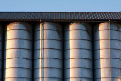 Line of silos. Row of metal silos under a roof with radent sunlight with contrast and light reflex Royalty Free Stock Images