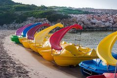 Line of six colorful pedalos. Pedalos on the sandy shoreline of the Menorca beach royalty free stock image