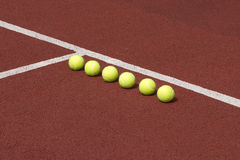 Line of six yellow tennis balls on court Stock Photography