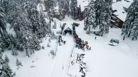 A line of skiers and snowboarders waiting to climb the lift Stock Image