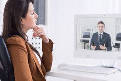 On-line solutions for everyday office work. Young smartly-dressed women in a modern, very bright office, having a video business call with a smiling young man Stock Images