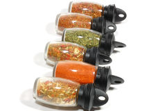 Line of spices glass bottles. Isolated on white Stock Photos