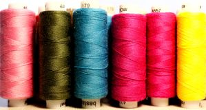 Line of spools of multicoloured threads royalty free stock photography