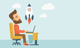 On-line start up. An enthusiastic, eager hipster Caucasian young man with beard sitting in front of his laptop browsing, researching  and planning a metaphor for Royalty Free Stock Photography