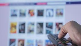 On-line-strömender Videoservice mit Apps und der Hand Smart Fernsehapparat Die männliche Fern Handholding die Steuerung drehen si stock video footage