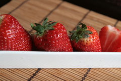 Line of strawberries in a white porcelain pot Royalty Free Stock Images