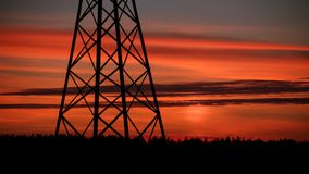 The line of support for electric gears against a sunset. Beautiful sunset of the October Sun royalty free stock photo