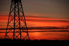 The line of support for electric gears against a sunset. Beautiful sunset of the October Sun stock photos