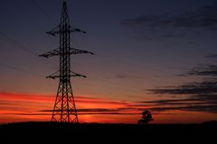The line of support for electric gears against a sunset. Beautiful sunset of the October Sun stock image