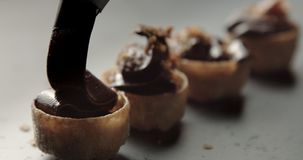 Line of tartlets full of chocolate cream and the last one is in process stock video