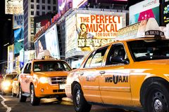 Times Square, New York City, New York, United States - circa 2012 line of taxi cabs in times square at night with theater marquees. Line of taxi cabs driving in Stock Photography
