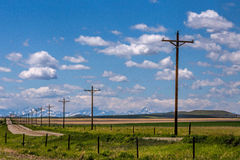 A Line Of Telephone Poles. This image was taken near Valier, Montana and shows a rural gravel road with a line of telephone poles and snowy mountains in the Stock Photos
