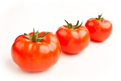 A line of three red tomatoes Stock Photography
