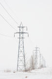 Line of Transmission Towers To Horizon in Winter Royalty Free Stock Image