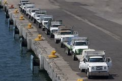 A line of trucks. On a pier waiting to transport stuff Stock Image
