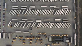 Line of trucks and trailers from above at a cargo terminal. Logistics center with trucks and trailers for cargo dispatching stock video
