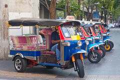 Line of tuktuks with driver on Bangkok street Stock Photos