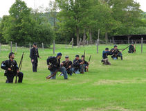 Line of Union Civil War soldiers. Skirmish line of Union soldiers in a field firing at the rebels during an American Civil War re-enactment battle.  Civil War re Stock Images