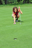 Line it up!. A pretty lady golfer lines up her putt on a golf green Stock Images