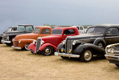 Line Up of Classic Automobiles Streetrods. A lineup of classic American automobiles including a 1938 Buick, 1933 Ford street rod, 1950 Chevy pickup truck lowered Royalty Free Stock Image
