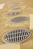 Line up of Sewer Drains. Uneven Line up of Sewer Drains on a sidewalk Royalty Free Stock Images