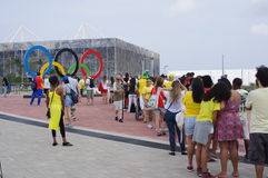 Line-up to take a picture with Olympic rings. In the background is the Olympic Aquatics Stadium in Barra Olympic Park during Rio2016 Olympics Royalty Free Stock Photo