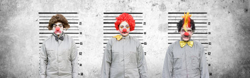 Line Up Of The Usual Suspects. A Male And Two Female Clowns Who Face Criminal Charges Lineup Against A Cement Wall In An Attempt To Find Out The Criminal Amongst Royalty Free Stock Image