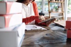 On-line-Verkäuferinhaber Sehr flacher DOF! Konzentrieren Sie sich auf der Hand und auf die Karte Stockfotos