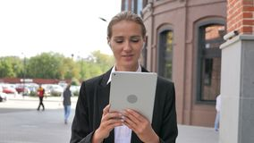 On-line-Videochat auf Tablet durch gehende Geschäftsfrau stock footage