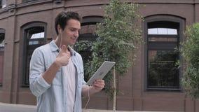 On-line-Videochat auf Tablet durch gehenden Mann auf Straße stock footage